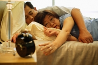 Mature couple sleeping in bedroom, woman reaching for alarm clock - Jade Lee