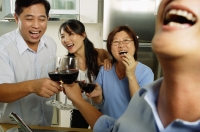 Two men and two women, in kitchen, toasting with wine glasses, laughing - Jade Lee