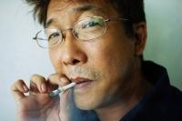 Man smoking cigarette, headshot - Jade Lee