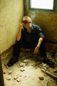 Man sitting corner, hand on head, smoking - Jade Lee