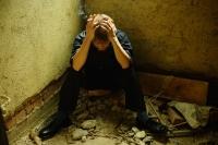 Man sitting in corner of empty room, hand on head - Jade Lee