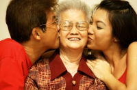 Three generation family, son and granddaughter kissing grandmother - Jade Lee