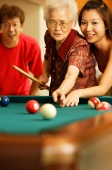 Father and daughter teaching grandmother to play pool - Jade Lee