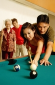 Couple playing pool, father and grandmother looking on - Jade Lee