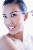 Woman looking at camera, using make-up brush - Alex Microstock02