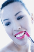 Woman applying lipstick, smiling and looking down - Alex Microstock02