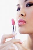 Woman holding lipstick, looking at camera - Alex Microstock02