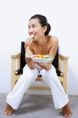 Woman sitting on chair, holding bowl of salad, smiling at camera - Alex Microstock02