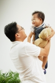 Father carrying young daughter up, smiling - Alex Microstock02