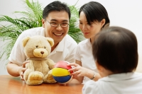 Father and mother with stuffed toy and ball, daughter looking at them, rearview - Alex Microstock02