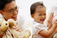 Young girl smiling, father next to her holding stuffed toy - Alex Microstock02