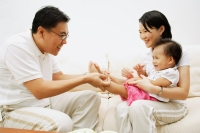 Family with one child sitting face to face, father holding daughter's leg - Alex Microstock02