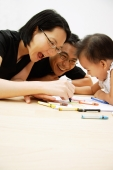 Family with one child drawing with crayons - Alex Microstock02