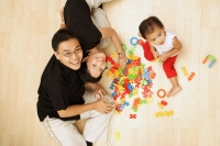 Family with one child sitting on floor looking at camera - Alex Microstock02