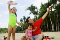Father with two girls, playing on beach with toy boat and toy plane - Alex Microstock02