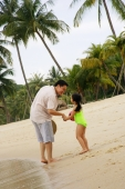 Father and daughter holding hands on beach - Alex Microstock02
