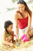 Mother with one child on beach, playing with sand - Alex Microstock02