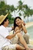 Couple sitting on beach, man holding mobile phone - Alex Microstock02