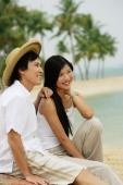 Couple sitting on beach, looking away - Alex Microstock02