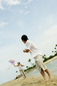 Couple flying kite along beach, man turning to look at woman - Alex Microstock02