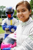 Young woman in sports jumpsuit, holding helmet, looking at camera, man behind her - Alex Microstock02