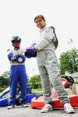 Young man and woman wearing motor racing jumpsuits, looking at camera - Alex Microstock02
