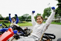 Young man and woman in go-carts, hands outstretched, smiling at camera - Alex Microstock02