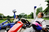 Young man and woman in go-carts, hands outstretched, smiling, looking away - Alex Microstock02