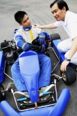Young man in go-cart, father crouching down next to him - Alex Microstock02