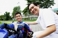 Young man in go-cart, father crouching down next to him, both looking at camera - Alex Microstock02