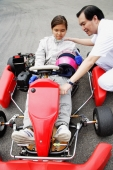 Young woman in go-cart, father crouching down next to her - Alex Microstock02