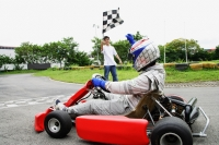 Young woman in go-cart, young man waving flag - Alex Microstock02