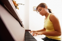 Young woman sitting at piano, looking down - Alex Microstock02