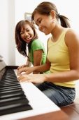 Mother and daughter sitting side by side in front of piano - Alex Microstock02