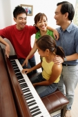 Family with two children, standing around piano, daughter playing piano - Alex Microstock02