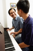 Father and son sitting at piano, looking at each other - Alex Microstock02