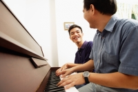 Father and son playing piano, side by side, looking at each other - Alex Microstock02