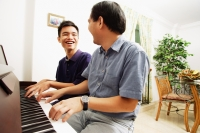 Father and son playing piano, sitting side by side - Alex Microstock02