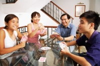 Family playing cards around table - Alex Microstock02