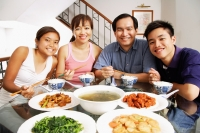 Family at home, sitting side by side, looking at camera, food on the table - Alex Mares-Manton