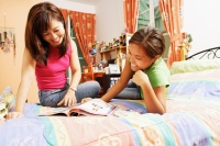 Mother with daughter, in bedroom, looking at magazine - Alex Microstock02
