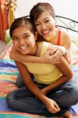 Mother hugging daughter, both smiling, looking at camera - Alex Microstock02