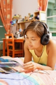 Young woman wearing headphones, looking at books - Alex Microstock02