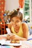 Young woman, lying on bed looking at mobile phone - Alex Microstock02