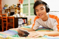 Young man listening to music, smiling at camera - Alex Microstock02