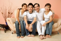 Family of four in living room, looking at camera, portrait - Alex Microstock02