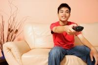 Teenage boy sitting on sofa, holding remote control, pointing at camera - Alex Microstock02