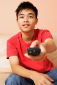 Teenage boy sitting on sofa, pointing remote control towards camera - Alex Microstock02