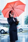 Business woman using mobile phone, holding umbrella - Alex Microstock02
