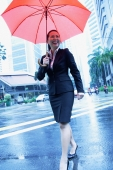 Business woman holding umbrella, walking across the road - Alex Microstock02